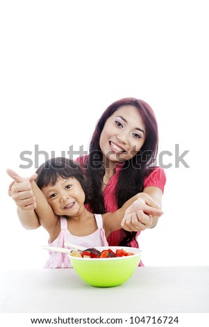 Happy mother and daughter with fruit salad showing thumbs-up - stock photo
