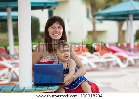 happy mother and  daughter   with laptop   at resort hotel area