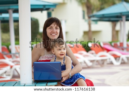 happy mother and  daughter   with notebook   at resort hotel area