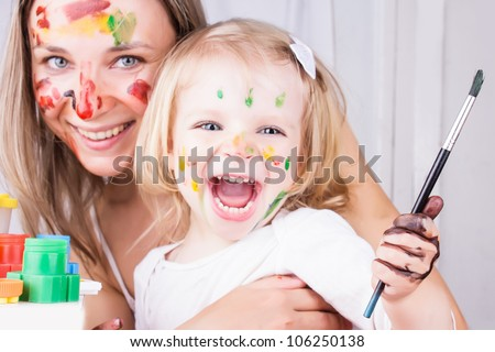 Happy mother and daughter with paint on faces, focus on baby - stock photo