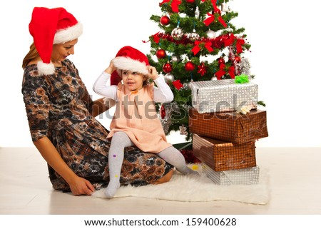 Happy mother and daughter with Santa hats sitting near Christmas tree - stock photo