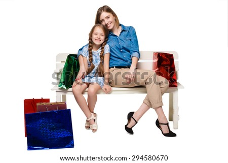 Happy  mother and daughter with shopping bags sitting at studio, isolated on white background - stock photo