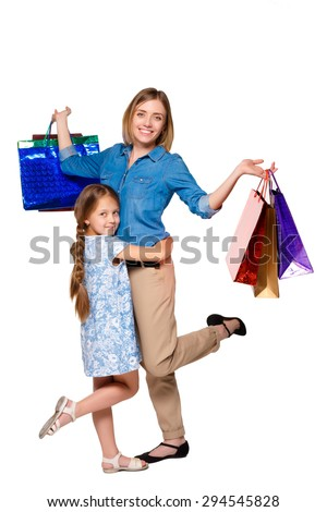 Happy  mother and daughter with shopping bags standing at studio, isolated on white background.  daughter hugging her mother - stock photo