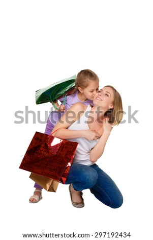Happy  mother and daughter with shopping bags standing at studio, isolated on white background.  daughter kissing mum - stock photo