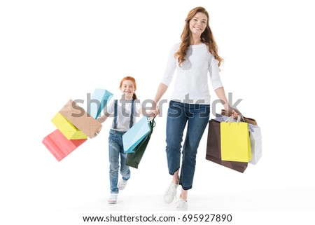 happy mother and daughter with shopping bags walking together isolated on white