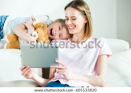 Happy mother and daughter with teddy bear using digital tablet at home