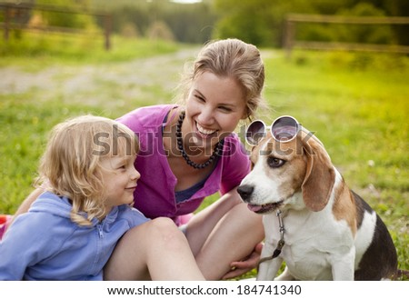 Happy mother and daughter with their dog beagle sitting on the grass in green park - stock photo