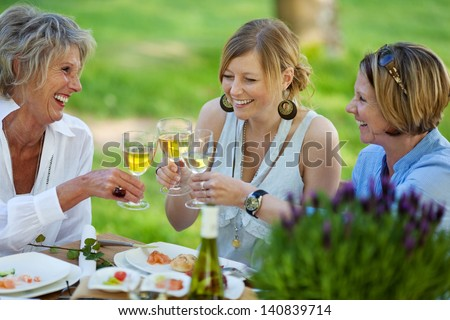 Happy mother and daughters toasting white wine at dining table in lawn - stock photo