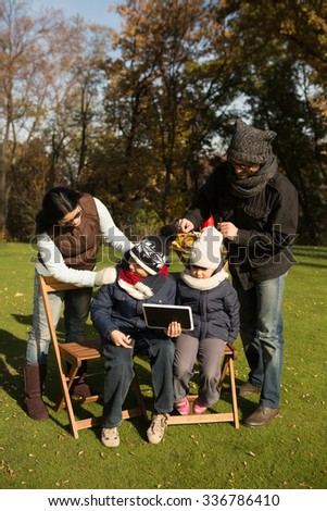 Happy mother and father adjusting their children hats while they are sitting on the wooden chairs with tablet PC. Young family spending time in the park.