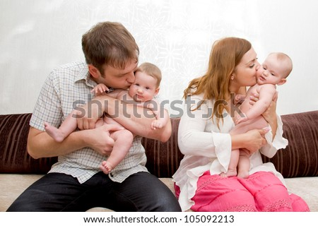 Happy mother and father kissing and laughing with two tiny babies twin sisters girls. Big Family