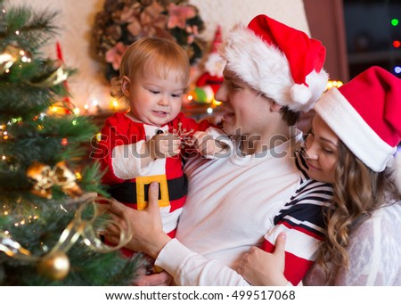 Happy mother and father with baby boy near Christmas tree
