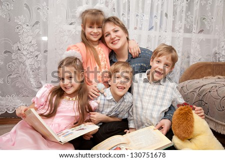 Happy mother and four children reading a book. Big family. - stock photo
