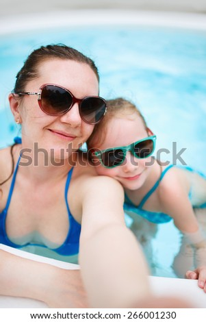 Happy mother and her adorable little daughter at outdoors swimming pool taking selfie on tropical vacation - stock photo