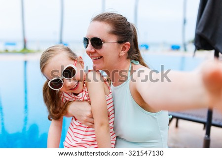 Happy mother and her adorable little daughter outdoors on vacation near a swimming pool taking selfie at tropical resort - stock photo