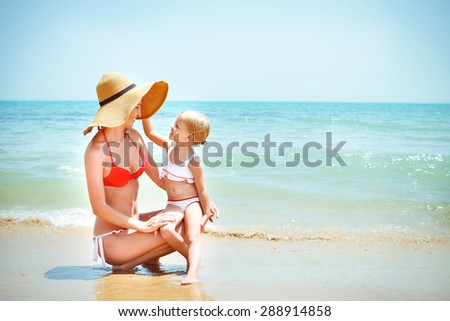 Happy mother and her baby daughter on sea coast. Summer holiday concapt - stock photo