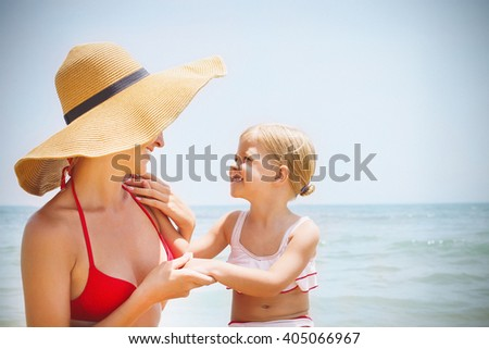 Happy mother and her baby daughter on sea coast. Summer holiday concept