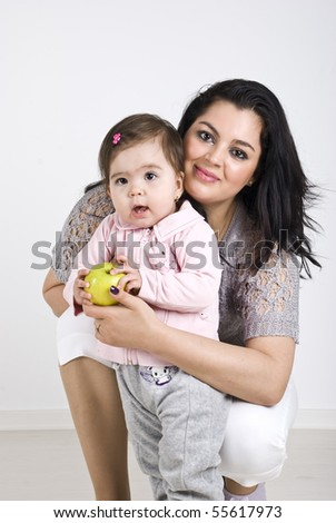 Happy mother and her baby girl 11 months old posing together