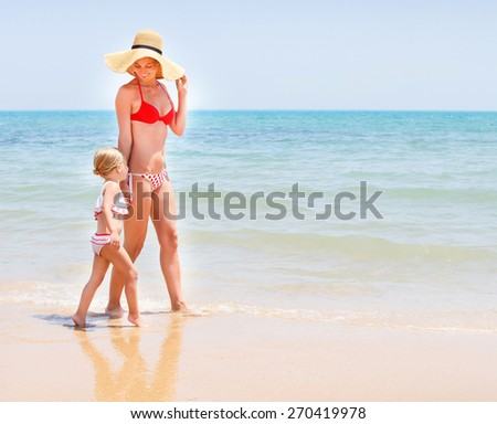 Happy mother and her baby girl running on sea coast - stock photo