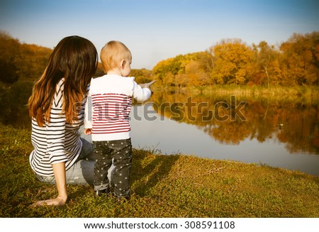 Happy mother and her baby on autumn lake - stock photo