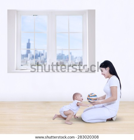 Happy mother and her baby playing colorful ball at home - stock photo