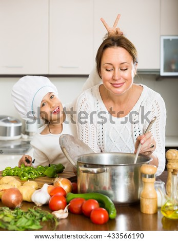 Happy mother and her cheerful daughter preparing soup at domestic kitchen. Focus on woman - stock photo
