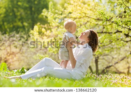 Happy Mother and her child enjoy the summer