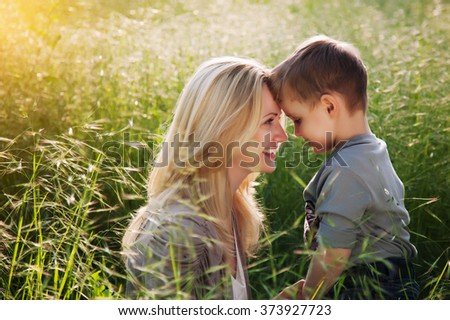 Happy mother and her child having fun outdoor under sunset.