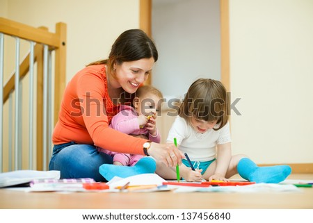Happy mother and her children drawing on paper - stock photo