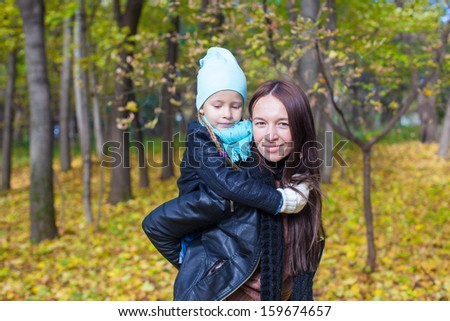 Happy mother and her cute daughter having fun in yellow autumn forest on a warm sunny day