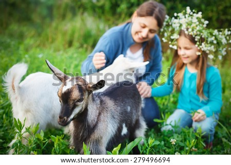 Happy mother and her daughter with baby goats on the countryside - stock photo