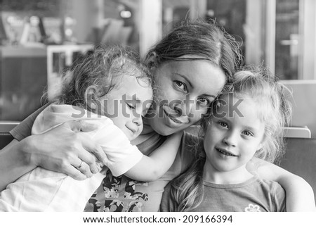 Happy mother and her daughters hug each other - stock photo