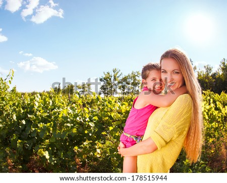 Happy mother and her little daughter in the harvest time in the vineyard - stock photo