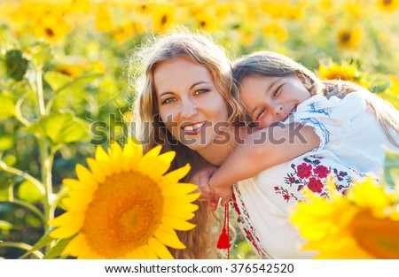 Happy mother and her little daughter in the sunflower field. Summer fun - stock photo