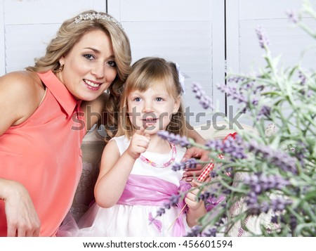 Happy mother and her little daughter with decorative heart sitting on sofa in provence style interior - stock photo
