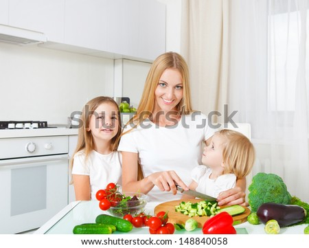 Happy mother and her little daughters cutting vegetables in the kitchen - stock photo