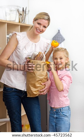 Happy mother and her Little girl unpacking grocery bag in the kitchen - stock photo