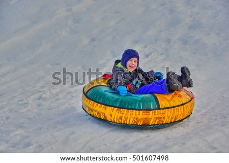 Happy mother and her son enjoying a winter sleigh ride on a slope