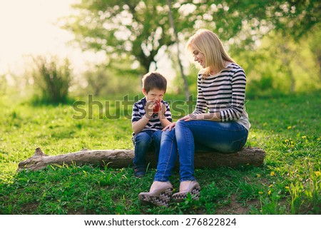 happy mother and her young son sitting on a tree in the park and eat a big red apple