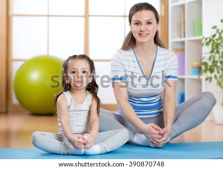 Happy mother and kid daughter spends time in the gym