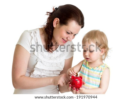happy mother and kid put coins into daughter's piggy bank - stock photo