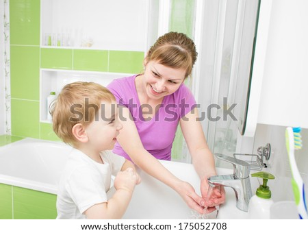 Happy mother and kid washing hands with soap together in bathroom - stock photo