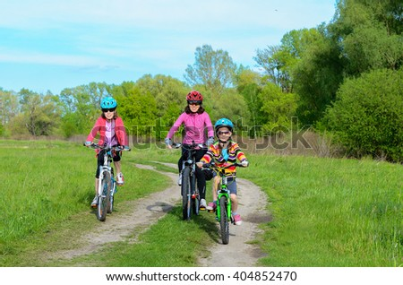 Happy mother and kids on bikes cycling outdoors, active family sport  - stock photo