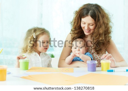 Happy mother and kids painting with gouache - stock photo