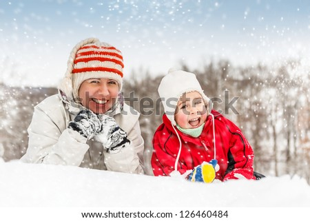 Happy mother and little boy lying in snow - stock photo