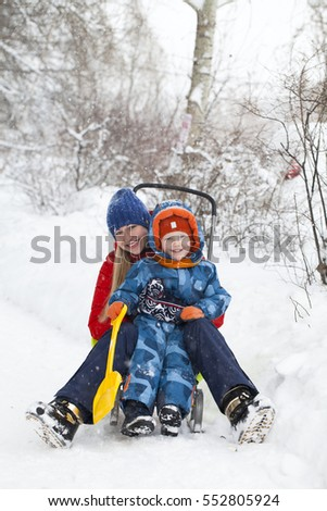 Happy mother and little boy playing in a snow in winter park