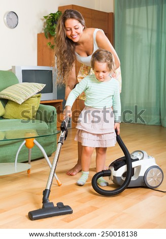 Happy mother and little daughter are doing house cleaning. Focus on woman