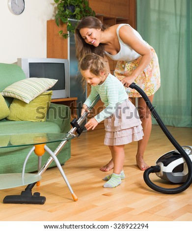 Happy mother and little daughter chores with vacuum cleaner in home. Focus on girl