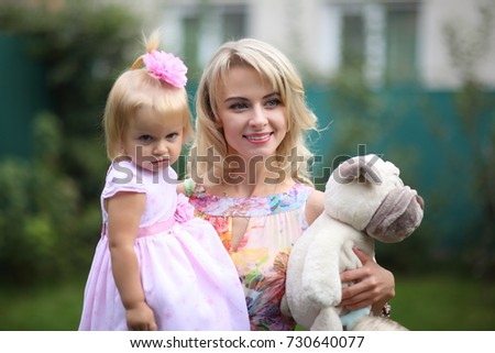 Happy mother and little daughter in her arms with a soft toy. Happy mother and little daughter with a smile posing for the camera.