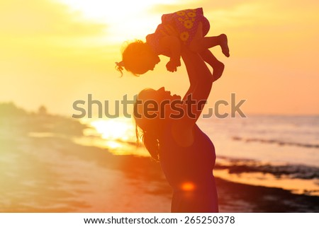 happy mother and little daughter play at sunset - stock photo