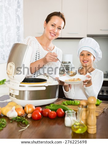 Happy mother and little daughter prepare rice in multicooker at kitchen - stock photo